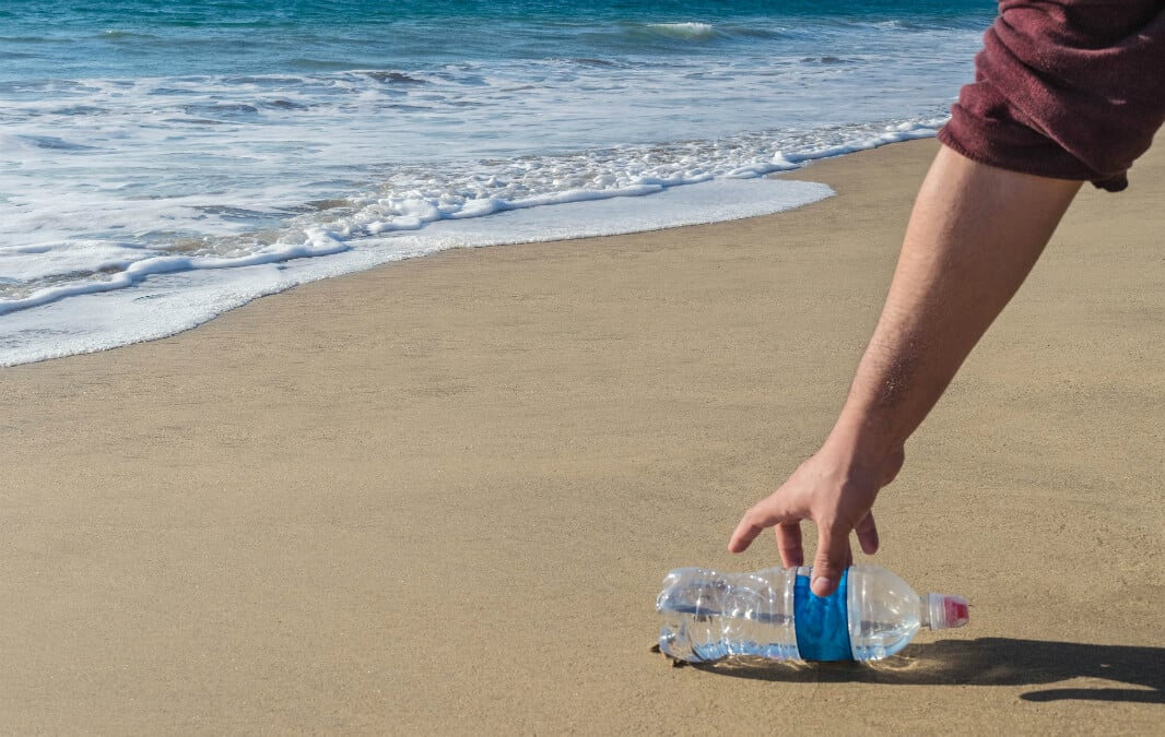 a hand picking up empty water bottle on the beach